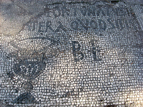 """Ostia Antica: Detail from the floor mosaic of a tavern; the word """"BIBE"""" written around the cup urges customers to drink"""